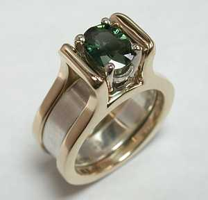 14kt Yellow Meghan reverse cradle set with an Oval Green Sapphire. Sterling Silver Filler Band